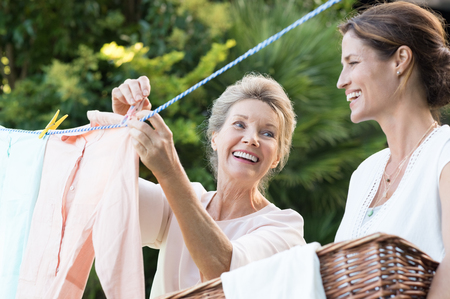 Older mother and young daughter hanging clothes outdoor to dry. Smiling daughter helping mother with laundry. Cheerful mother and daughter in conversation while hanging clothes outside. Stock Photo