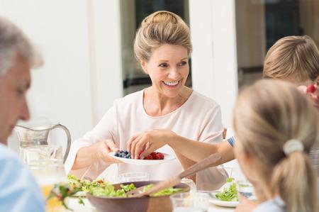 alimentos saludables: abuela Alegre sirve la fruta a los nietos. Mujer mayor que ofrece alimentos a nieto y nieta. Niño pequeño recogiendo las cerezas de la placa de frutas durante el almuerzo. Foto de archivo