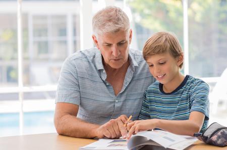 tarea escolar: El abuelo que ayuda granchild completar su tarea. hombre mayor que asiste a su nieto con el estudio. El abuelo muchacho de ayuda con el trabajo en clase como en casa. Foto de archivo