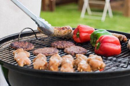Close up of food on grill barbecue. Barbeque in garden for family. Close up of hamburgers, sausages and peppers cooking on barbecue.