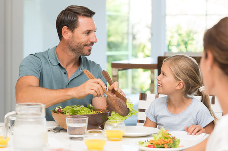 serve: Happy father serving salad to daughter. Small young family enjoying lunch at dining table. Daughter asking father to serve food.