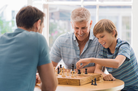 Grootvader onderwijs kleinzoon hoe te schaken. Vader en zoon spelen schaak met kleinkind. Grootvader kijken naar zoon en kleinzoon spelen bordspel thuis.