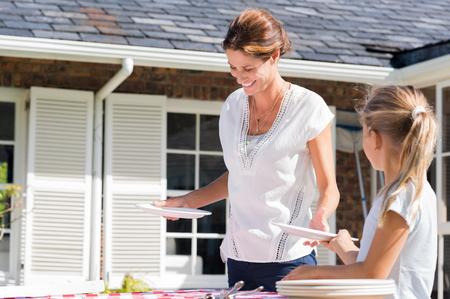 Vrolijke jonge moeder regelen borden op tafel buiten het huis. Dochter helpt moeder regelen van de tafel op de binnenplaats. Dochter geven borden aan moeder.