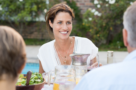 lunch meal: Happy cheerful woman sitting with family enjoying meal. Happy mature woman sitting at dining table outdoor with her family. Portrait of a happy young cheerful woman eating lunch with parent and child.