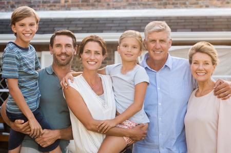 Portrait de la famille élargie gaie debout à l'extérieur de leur maison. Happy family debout à l'extérieur et en regardant la caméra. Les parents avec les grands-parents e les enfants bénéficiant des vacances ensemble.