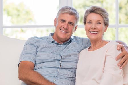 Usmívající se senior žena a muž sedí spolu na pohovce. Portrét upřímného staršího páru se těší jejich odchodu do důchodu doma. Šťastný úsměv starší pár objímat dohromady a díval se na kameru. Reklamní fotografie