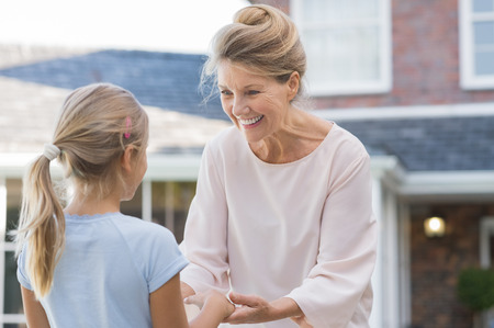 grandkid: Cheerful grandmother welcoming granddaughter to her house. Senior healthy woman delighted to see little girl in the garden outside house. Older woman and grandchild in a happy conversation.