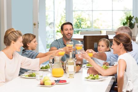 tomando jugo: generación de la familia sonriente levantando copas juntos en la cocina. padre feliz con los niños y los abuelos celebrando junto con una tostada. Familia alegre que levanta la tostada con el jugo en la mesa de comedor. Foto de archivo