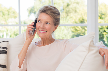 Hogere vrouw die op haar mobiele telefoon. Senior vrouw heeft een happy gesprek op mobiel. Glimlachend senior vrouw met behulp van de telefoon zitten op de bank thuis.