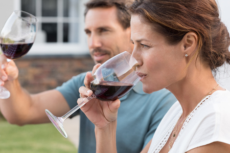 Portrait of young woman drinking red wine while man raising a toast. Mature couple enjoying drinks in the park. Couple enjoying picnic with wine.