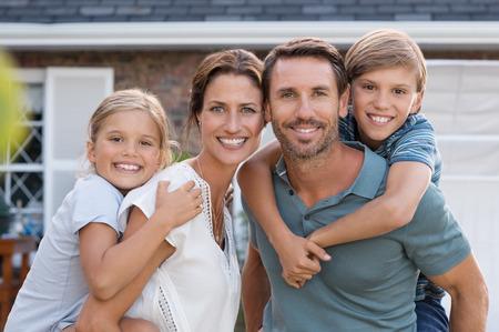 Ouders die op de rug rit naar kinderen. Gelukkige moeder en vader met zoon en dochter kijken naar de camera buiten het huis. Portret van gelukkige paar zich dragen op de schouder van hun kinderen.