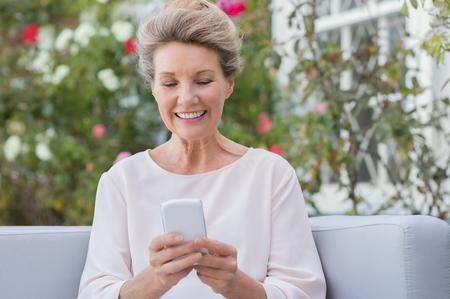 Hogere vrouw messagging met de mobiele telefoon tijdens de vergadering op de sofa in de tuin. Oudere vrouw texting een telefoon bericht met haar nieuwe smartphone. Stockfoto