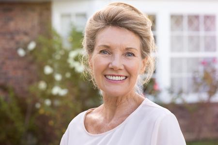 Gelukkige hogere vrouw die zich buiten haar huis. Content vrouw glimlacht en kijkt naar de camera. Portret van vrolijke oude grootmoeder ontspannen buiten het huis. Stockfoto