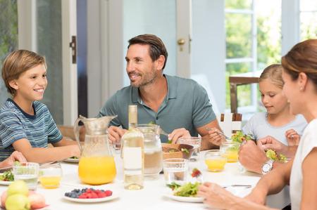 familias felices: Familia feliz que el almuerzo juntos. Familia de risa alrededor de una buena comida en la cocina. Los padres y los niños que comen la ensalada para el almuerzo. Foto de archivo