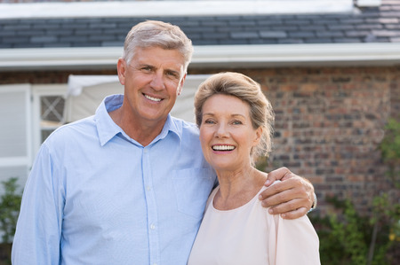 front house: Portrait of a happy senior couple smiling in front of their house. Older couple embracing and looking at camera. Happy old retired couple hugging.