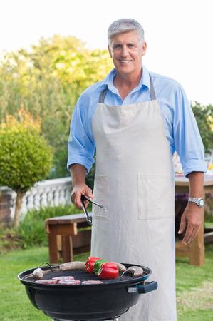 エプロンを身に着けていると庭の家の料理の年配の男性。彼の家族の屋外バーベキューで幸せの祖父。バーベキューを調理し、カメラ目線の老人の
