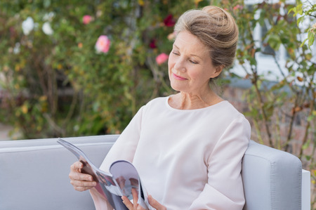 Senior woman reading a magazine sitting on a couch outdoor. Happy elderly woman reading a gossip magazine in her free time. Mature woman relaxing in the garden. Stock Photo