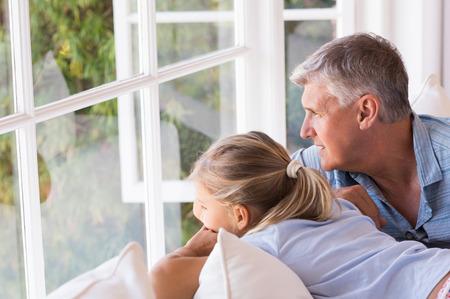 persona pensando: Niña mirando por la ventana con el abuelo. hombre mayor que se sienta con la niña cerca de la ventana y mirando hacia afuera. Abuelo y nieta pensar juntos. Foto de archivo