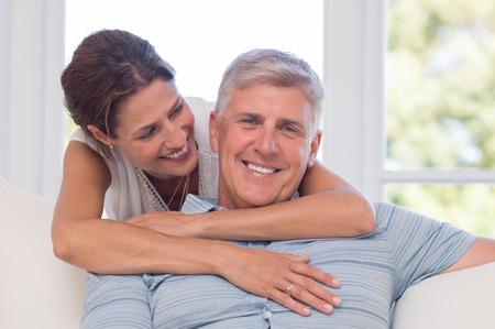 Portret van jonge vrouw omarmen vader van achter en lachend. Gelukkige vader en dochter die een tedere knuffel geven. Portret van volwassen dochter van achteren haar oudere vader knuffelen.