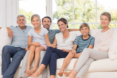 sons and grandsons: Portrait of happy family sitting on couch at home. Smiling parents, grandparents and happy children looking at camera. Portrait of extended family group sitting together.