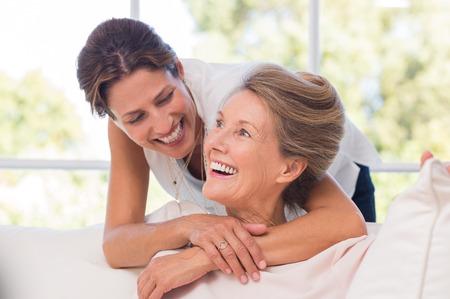 Portrét matka a dcera objímání. Šťastné senior matka a dospělá dcera zahrnuje doma. Veselá žena objímá starší žena a díval se na sebe.