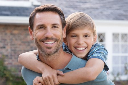 Portrait of young father giving piggyback ride to son and looking at camera. Happy father carrying his child on shoulder outdoor. Smiling son and father enjoying together.