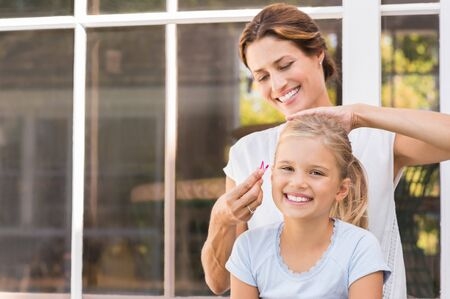 combing hair: Smiling young mom making the hair tail to her daughter. Cheerful mother applying clips to daughter hair. Portrait happy woman and little girl laughing together in a summer day.