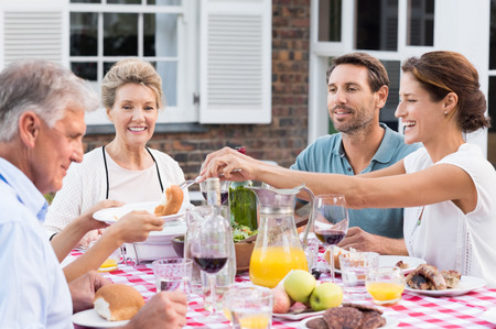 lunch meal: Happy family eating together outdoor. Cheerful woman serving bread to daughter. Smiling generation family sitting at dining table during lunch. Happy cheerful family enjoying meal together in garden.