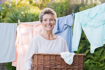 拿着在晒衣绳前面的快乐的资深妇女洗衣篮子。老妇人烘干衣裳画象。垂悬衣裳和看照相机的资深妇女。