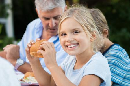 Junge hübsche Mädchen Brot genießen Essen und Blick in die Kamera. Kleines nettes Mädchen mit Bruder und Großvater, die Sandwich isst. Portrait eines jungen Mädchens, das Mittagessen mit der Familie auf Picknick.