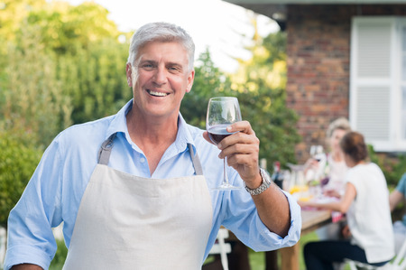 Happy old man wearing apron raising a toast. Senior man drinking a glass of red wine and looking at camera. Portrait of happy grandfather having lunch with his family outside.