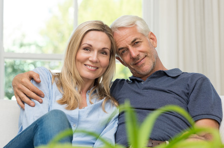Romantic senior couple sitting on a sofa and looking at camera. Portrait of a mature couple enjoying their retirement. Happy smiling senior couple embracing together at home. Zdjęcie Seryjne