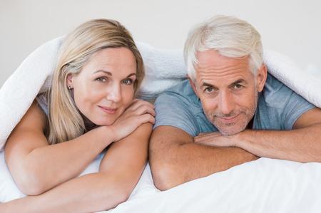 romance: Senior romantický pár pod bílou peřinou v posteli. Šťastný dospělý pár vleže na posteli a díval se na kameru. V důchodu muž a žena s úsměvem baví ležící na posteli doma. Reklamní fotografie