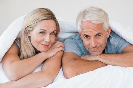romance: Starszy para romantycznych pod białą kołdrą w łóżku. Happy Starsza para leżąc w swoim łóżku i patrząc na kamery. Emerytowany mężczyzna i kobieta uśmiecha zabawy leżąc na łóżku w domu.