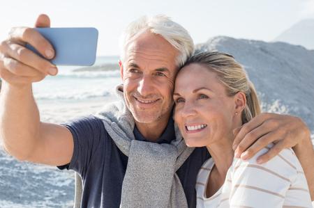 Gelukkig romantisch paar die op het strand omhelzen en een foto met slimme telefoon nemen. Portret van hoger glimlachend paar die een selfie in een de zomervakantie op zee nemen. Het gelukkige rijpe paar neemt een beeld bij zonsondergang. Stockfoto
