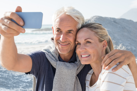 Happy romantic couple embracing on the beach and taking a photo with smart phone. Portrait of senior smiling couple taking a selfie in a summer vacation at sea. Happy mature couple take a picture at sunset.