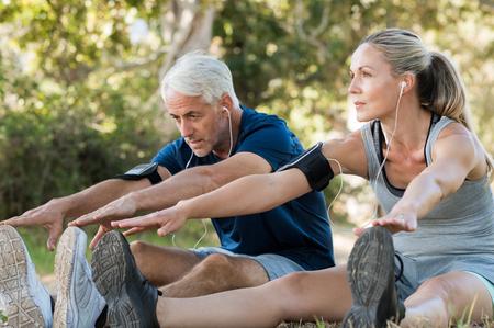 Ouder stel dat op het park strekt en muziek luistert. Atletisch senior paar uitoefenen buiten elkaar. Fit senior runners uitrekken voordat ze buiten lopen.