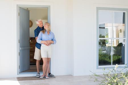 Glücklich reife Paar vor der Tür umarmen. Lächelnd, glücklich älterer Mann und Frau, die einander auf der Schwelle des neuen Hauses suchen. Lächelnder Mann umarmt Frau.