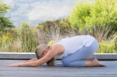 La femme dans les vêtements de sport performants yoga dans l'enfant pose. Détendu femme âgée exerçant le yoga asana. femme d'âge mûr étirement tout en pratiquant le yoga en plein air.