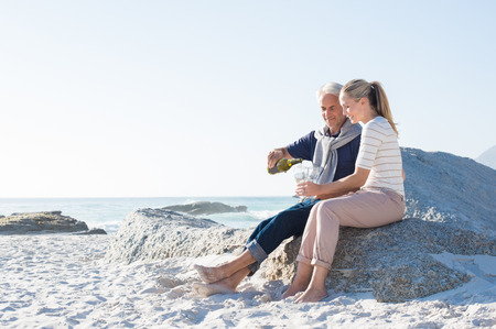 anniversary beach: Senior man pouring white wine in glasses for celebrating anniversary with his wife. Happy mature couple sitting on beach while man filling glasses of wine. Smiling couple enjoying white wine at beach. Stock Photo