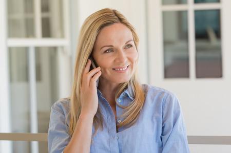 Fröhlich reife Frau im Gespräch über Telefon im Freien. Glücklich Mitte Frau mit Handy. Frau in einem glücklichen Gespräch über Smartphone. Lächelnde Frau am Telefon. Standard-Bild