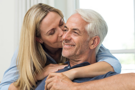 old women: Senior woman embracing her husband from behind. Close up face of mature woman kissing man on cheek in living room. Portrait of a loving wife kissing senior man. Stock Photo