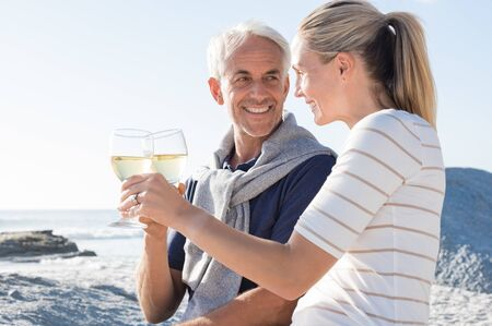 Happy romantic mature couple enjoying glass of white wine on the beach. Cheerful senior couple raising a toast celebrating wedding anniversary. Stock Photo