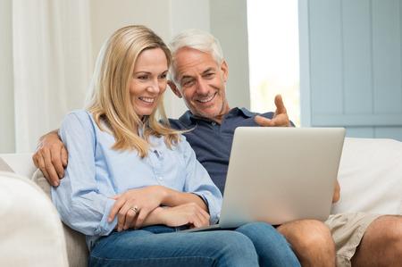 Hombre maduro y su esposa trabajan con el portátil en casa. Pares mayores usando el comercio electrónico en internet con el equipo. matrimonios de edad alegre sentado en el sofá en casa y usando la computadora portátil. Foto de archivo