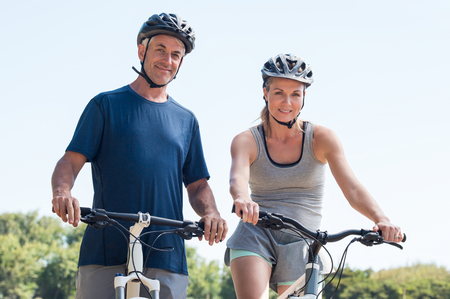 coutryside: Smiling mature couple on a mountain bike wearing sports clothes and looking at camera. Senior couple riding a bike together. Athletic couple enjoying cycle ride and looking at camera.