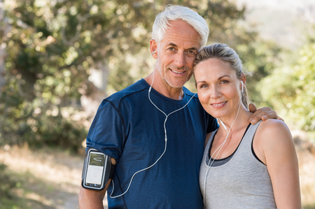 Portrait of senior sports couple looking at camera. Happy mature couple relaxing after jogging in the park. Smiling woman and retired man jogging and listening to music with earphones.