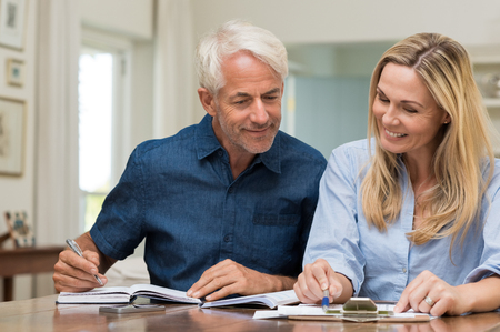 financials: Mature couple doing family finances at home. Senior couple discussing home economics sitting at table. Happy couple sitting at home planning household financials.