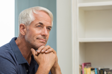Portrait of thoughtful senior man at home. Pensive retired man smiling and looking up. Happy mature man thinking about his retirement. Imagens