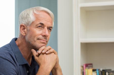 Portret van doordachte senior man thuis. Nadenkend gepensioneerde man lacht en kijkt omhoog. Gelukkig volwassen man na te denken over zijn pensioen.