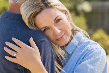 Close up face of a loving woman embracing senior man. Portrait face of mature romantic couple hugging outdoor. Closeup face of senior woman embracing husband in park.